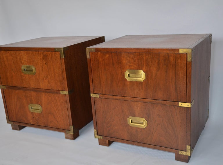 Pair of Campaign style mahogany nightstands by Baker Furniture. In outstanding condition, this pair features recessed brass Campaign handles and corner detailing on both the front and sides. Both nightstands have ample storage with the top