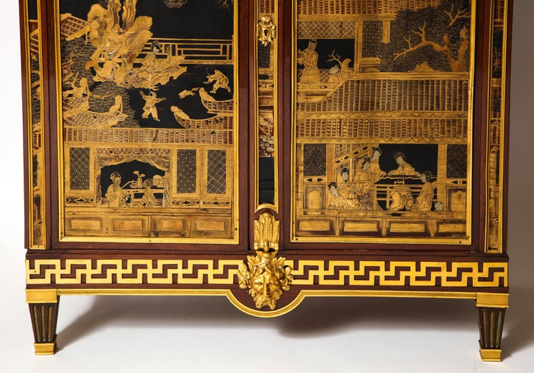 A spectacular antique French Louis XVI style gilt bronze mounted mahogany Chinese lacquered double door cabinet embellished with Chinese gilt decorated lacquered panels depicting chinoiserie scenes and further mounted with fine gilt bronze detail,