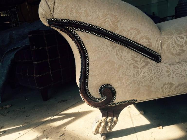 Late Victorian chaise longue upholstered in Fortuny style fabric. Nailhead trim border and carved wood feet which are partially gilded. Style of feet referred to as hairy paw feet as they resemble a lion's paw.