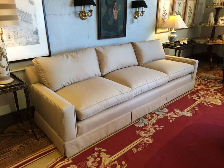 Beautifully made custom sofa, quite long and sleek in stature, having three-seat cushions and three back cushions, upholstered in a neutral light tan solid fabric.