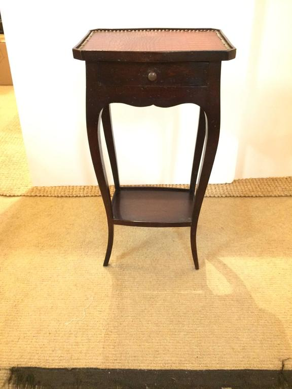 Masculine Italian ebonized walnut side or end table having single drawer, lower tier with wooden gallery surround, elegant curved legs, and a smashingly stylish faux alligator top finished with nailheads.
