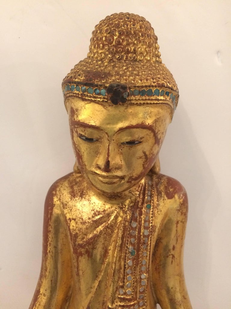 Medium sized beautiful carved giltwood Buddha with meticulous detail and glittery rhinestone decoration across the top of robe.
