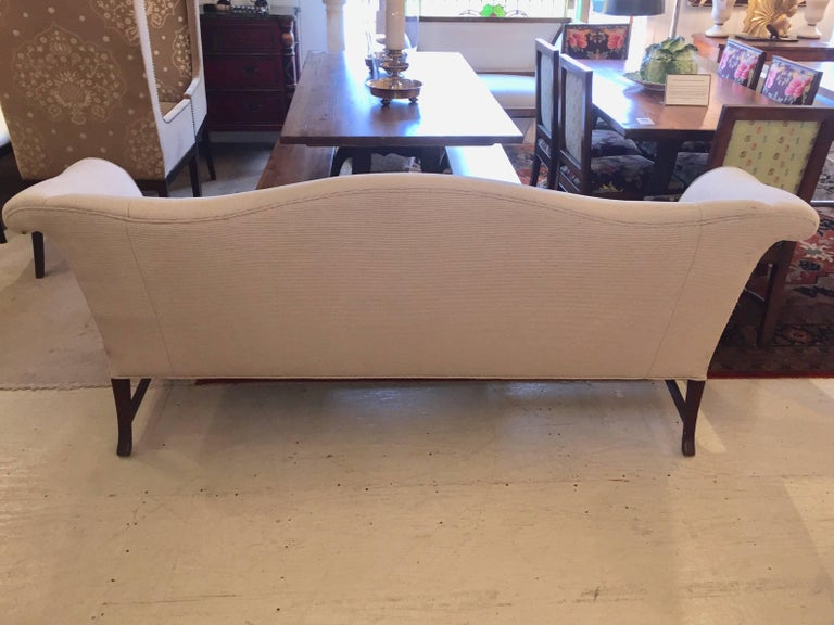 Wonderfully shaped classic camel back sofa having mahogany legs and stretcher, upholstered in a neutral taupe fabric. Back of sofa has some pulls, so best if it will be used against a wall or otherwise reupholstered.