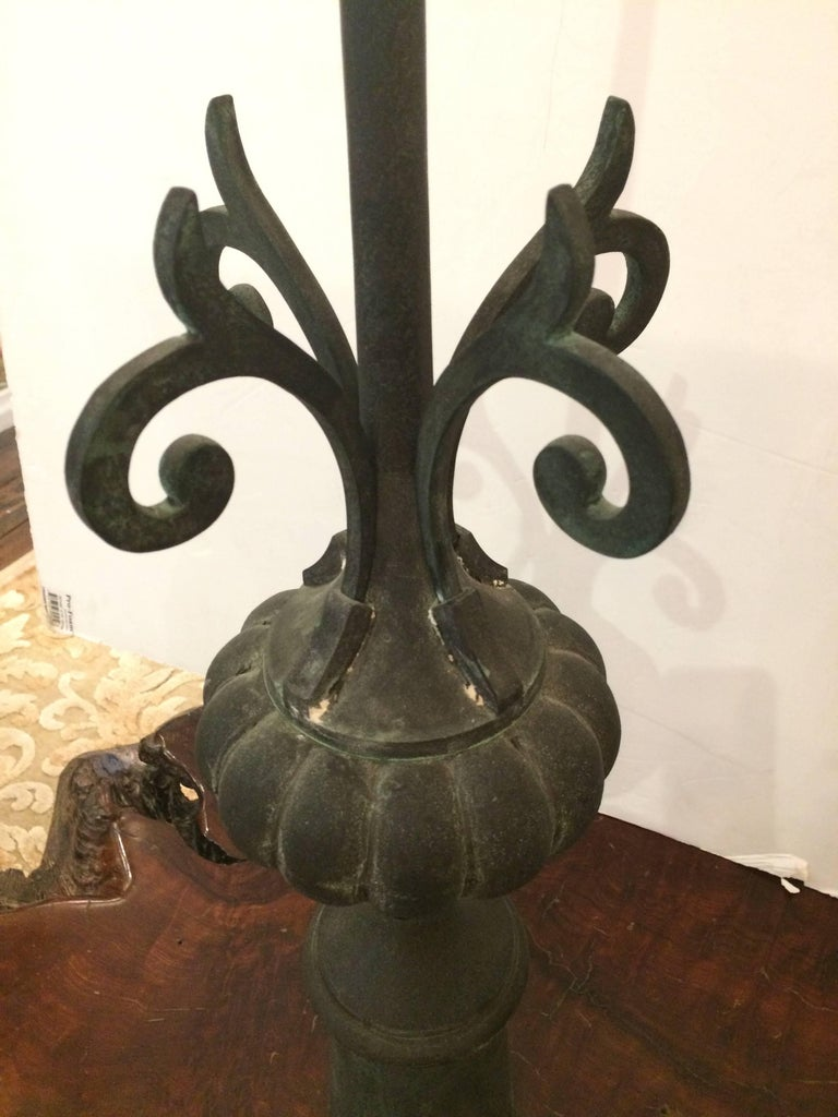 Two handsome dark grey iron finials having a central tall spike and curlicues on a fluted bulb and column base. Have an aged appearance.