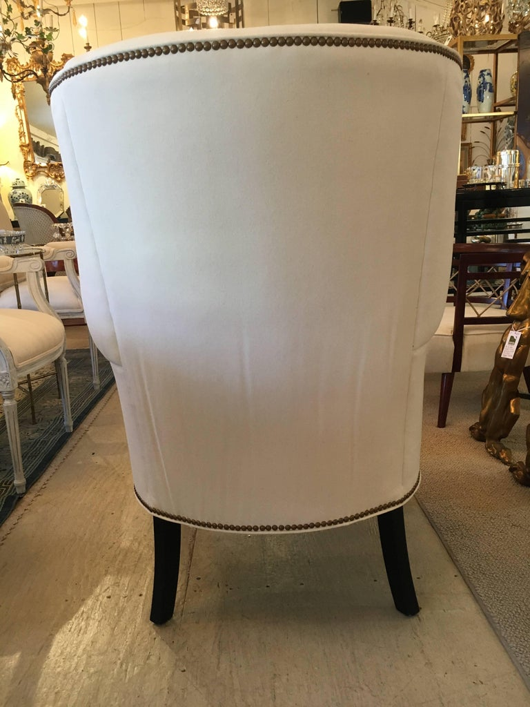 Sophisticated pair of wing chairs with ebonized legs newly upholstered in white cotton duck and
