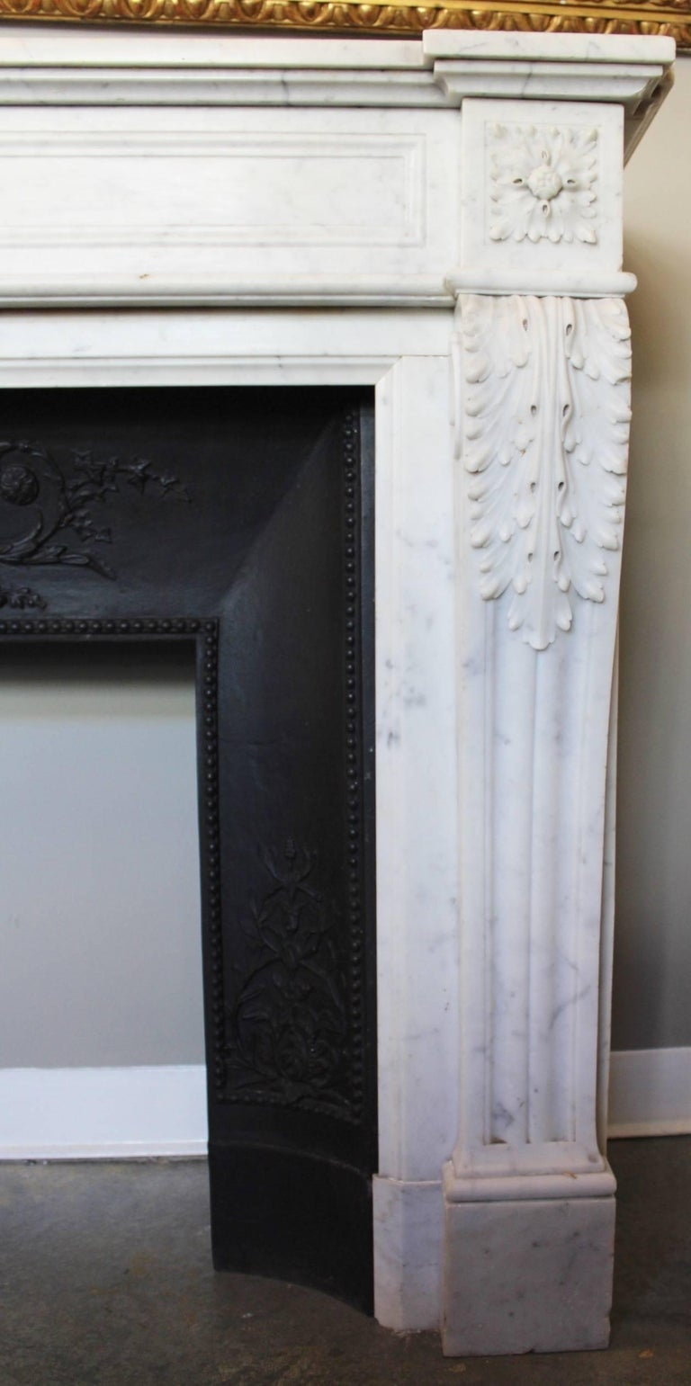 Supremely elegant antique fireplace mantel in white Carrara marble, the quality of the sculptures is enhanced by the starkness of the Carrera. Large carved Acanthus leaves are covering the top of the arched jambs resting on fluted console feet that