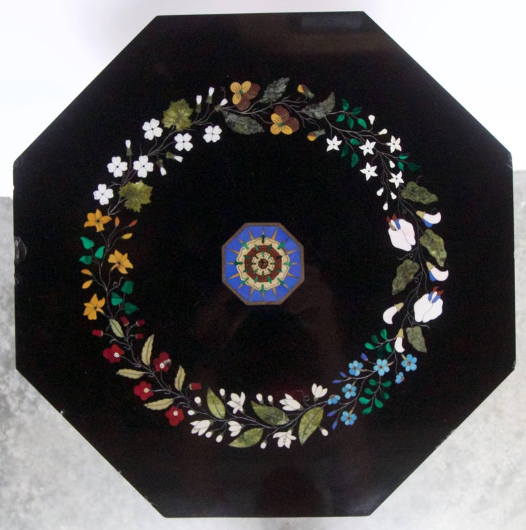 A very fine mid-19th century Florentine pietra dura inlaid decor on an octagonal black Belgian table marble top. The pietra dura inlay depicting a colorful circular guirland of flowers and foliage made of semi precious hardstones such as malachite,