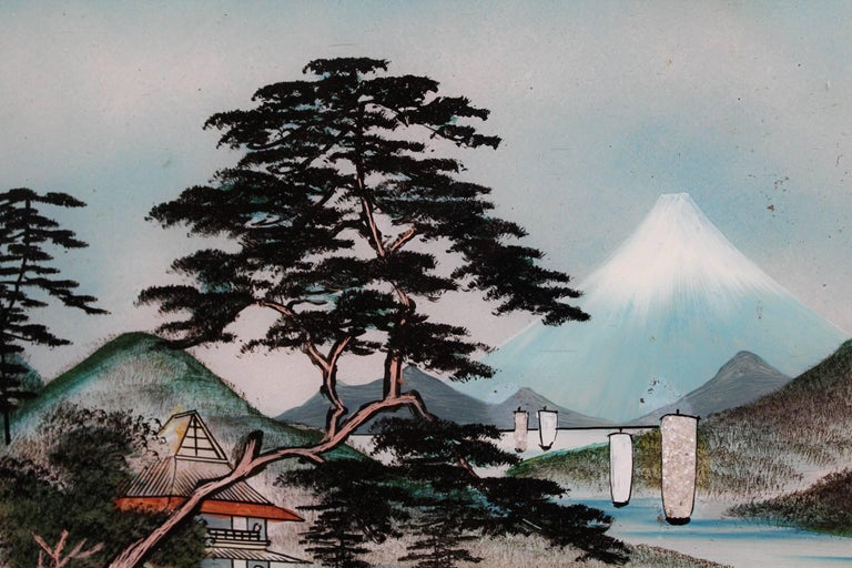 Fine early 20th century pair of Japanese reverse glass painting landscapes featuring each a lake surrounded by hills and houses with high trees. On one of these, the upper right background shows the Mount Fuji, symbol of Japan.