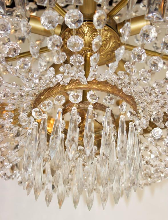 Corbeille (Basket) chandelier in gilt bronze and crystal with ten outside light arms and five inside. Under the twelve palmates gilt bronze crown flows out a string Cascade of diamond-shaped cutted crystals joining a large chased brass belt