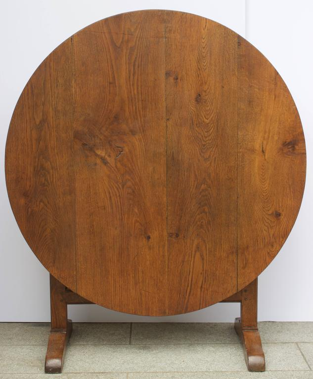 Lovely round oak wine table from burgundy with a handsome swivel lyre pedestal permitting to straight up the table against a wall when not in use providing space to the crowded cellar. Rest on two sledge feet.