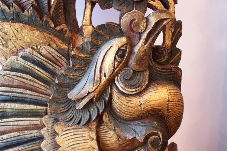 This pair of colorful and extraordinary roosters were hand-carved from single wood blocks, gilded and painted as Architectural elements of homes. Each rooster, surrounded by flowers and leaves shows-off its polychrome magnificent feathers and sort
