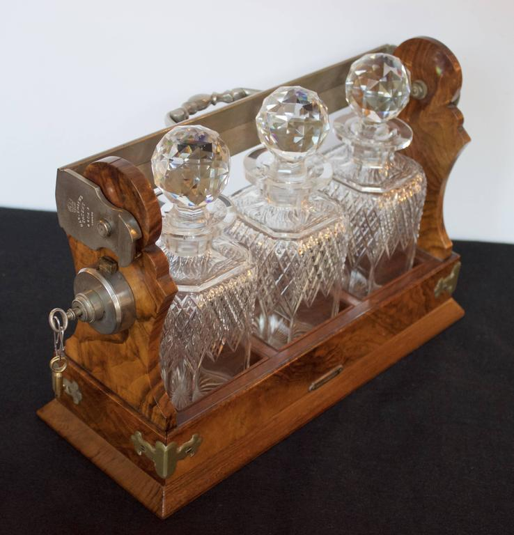 """The Tantalus Betjemann's Patent 46043 London"" stamped locking handle with the original three gorgeous and intact cut crystal decanters and their stoppers resting in a crotch mahogany case marked ""Kirby Beard&Co"" on a brass plaque.