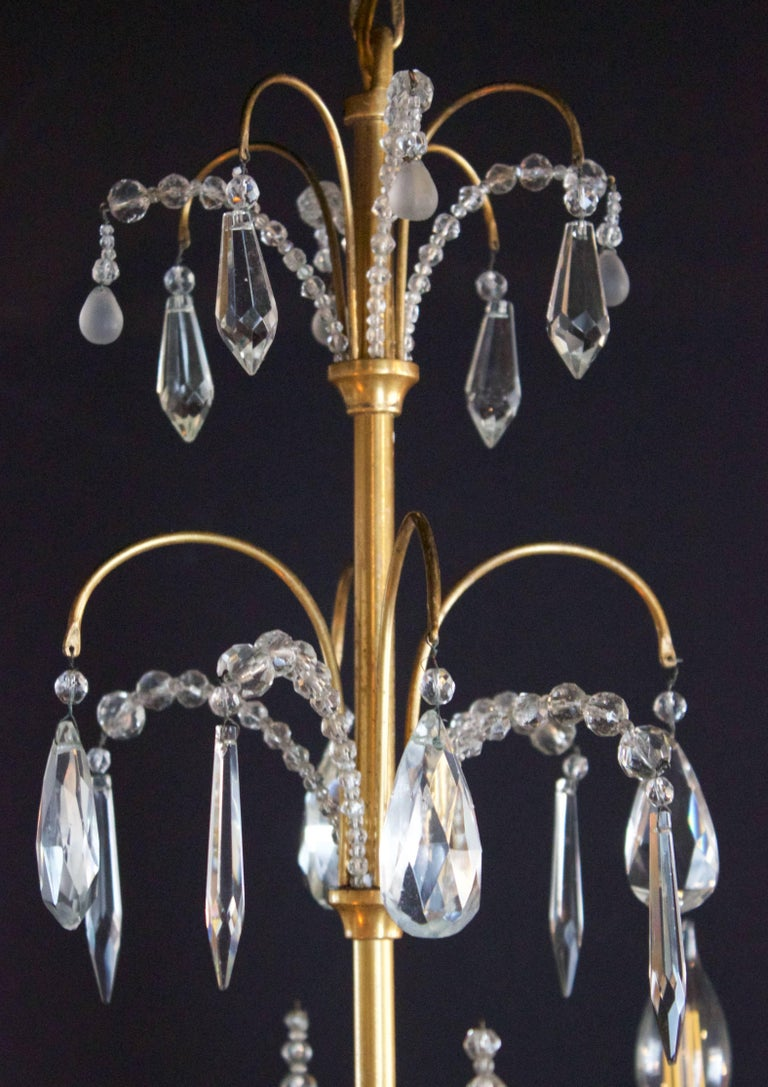 Very elegant bronze and crystal chandelier by Maison Jansen. Four scrolled light arms ending by flowers beads decorated cups as bobeches. Graduated and faceted superb crystal decor.