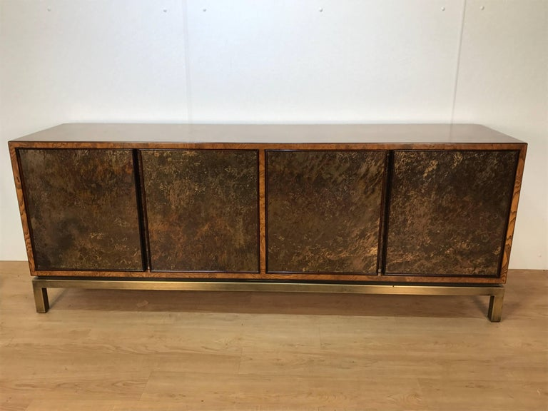 Stunning acid washed bronze sideboard by John Widdicomb, of rectangular form, the burled elm case is fitted with four concealed acid washed bronze doors raised on a patinated brass campaign style base. Expertly finished.