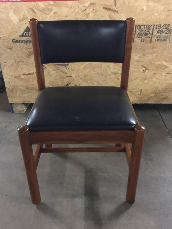 12 Danish Walnut Dining Chairs, each one in rich walnut with rectangular back rest with flanking circular columns, with conforming seat and legs. Upholstered in original black naugahyde.