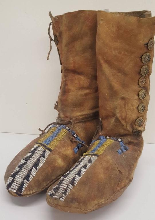 A pair of high button, deerskin moccasins of a Plains Native American tribe. Beaded by hand on each moccasin top, in yellow and blue above a black and white saw tooth band or strip of period beads, down to the toe. There is a row of machine made