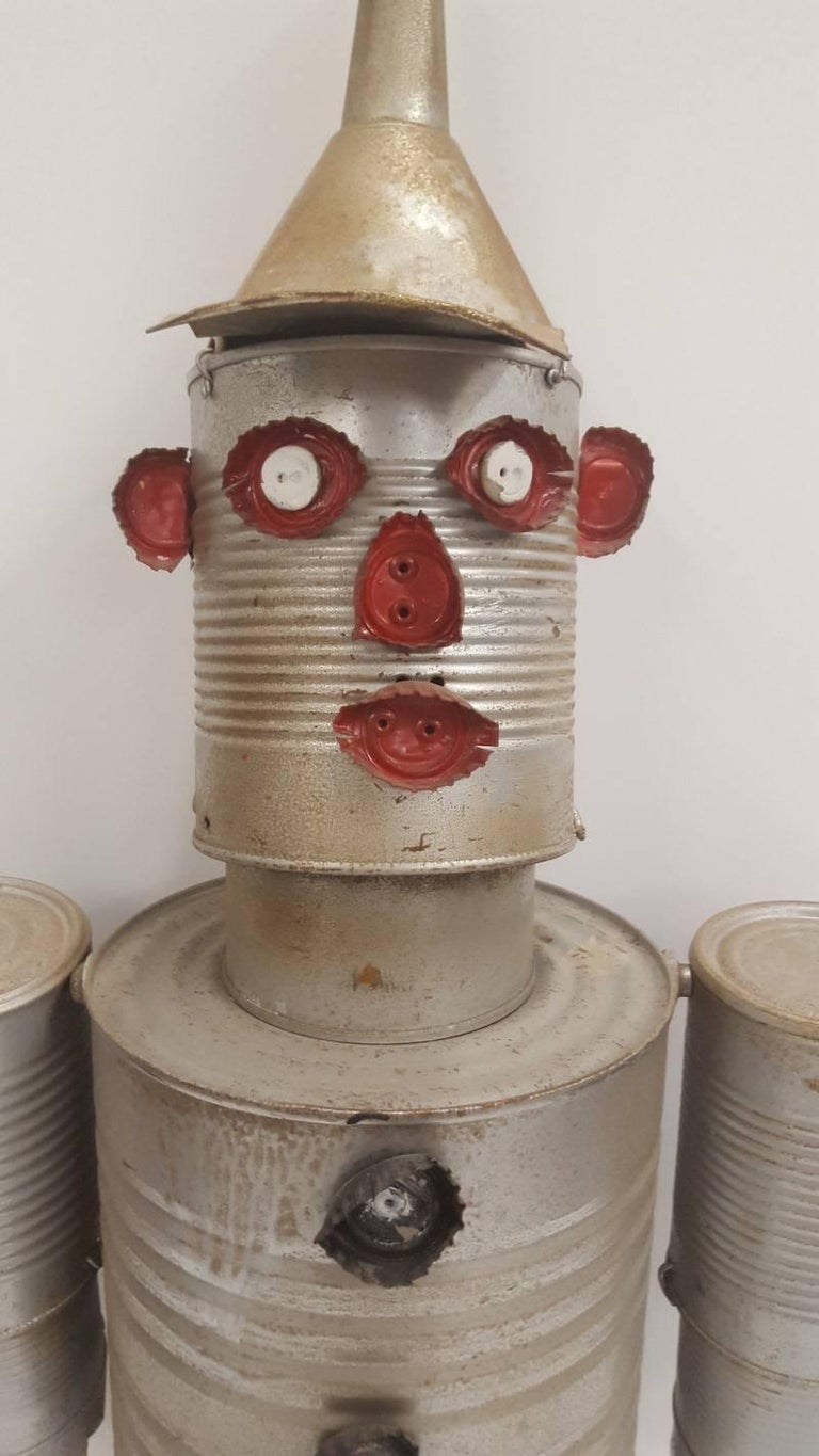 A sculptural figure made from tin cans, bottle tops, paint, wire, and rivets. It has moveable joints due to the cans being connected with wire and some rivets. It is a charming collectable, which could be used as a decorative wall hanging. It was