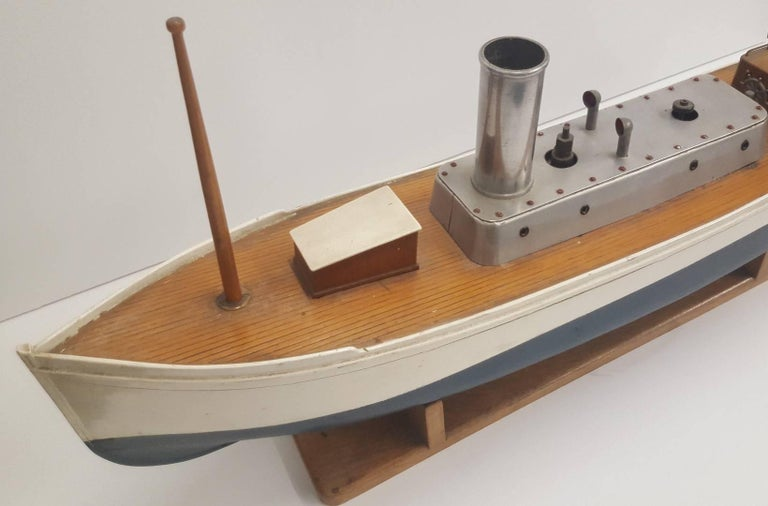 Painted model pond boat powered by a steam engine. Owned by current collector over 25 years without ever sailing the model. Metal (perhaps aluminium) centre parts on upper deck, including smoke stack, hand wheel, rudder, and air vents. Beautiful