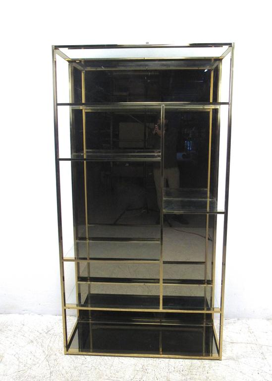This unique brass finish etagere offers plenty of stylish storage or display space, complete with staggered size shelves for added variety. Unique smoked mirror background and bottom shelf add a nice vintage touch to the piece. Please confirm item