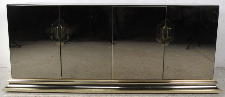 Stylish modern sideboard featuring mirrored body with beautifully sculpted brass trim. Tinted mirror finish adds to the elegant appeal of this storage credenza, offering perfect shelf storage for any application.  Please confirm item location NY or