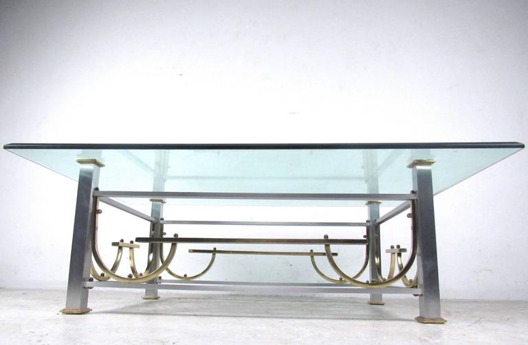 This unique vintage coffee table features a stylish vintage base with four post design, beveled glass and brass trim. Great table for a variety of modern interiors, please confirm item location (NY or NJ).