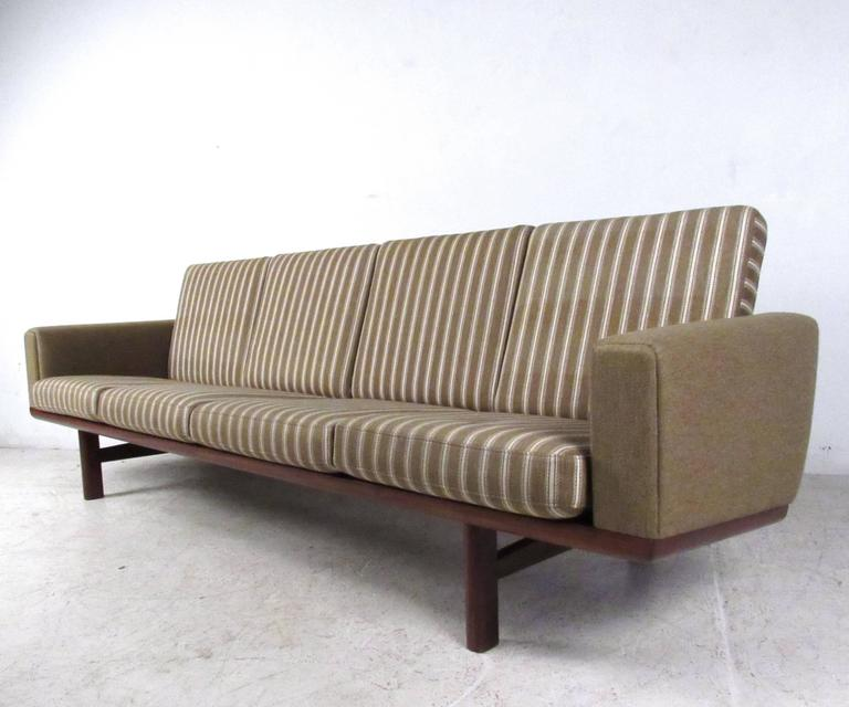 This beautiful vintage four seat sofa offers a stylish seating solution for a variety of interiors. Wegner's unique slat back design pairs wonderfully with the piece's straight lines, vintage fabric and spacious seats. Designed by Hans Wegner for