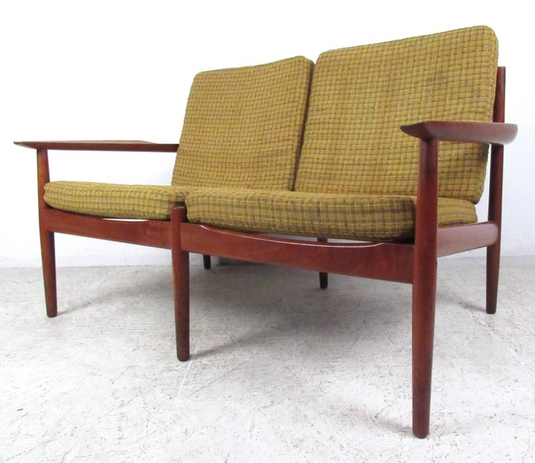 This Danish vintage two-seat offers a stylish teak finish with a uniquely sized two-seat settee. By Arne Vodder, this seating option is perfect for home or office setting. Please confirm item location (NY or NJ).