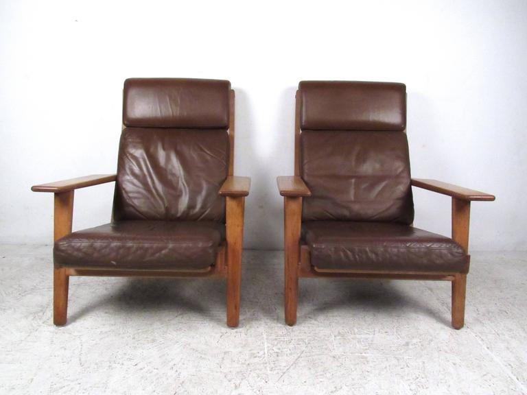 This beautiful vintage pair of brown leather lounge chairs feature the unique Mid-Century style of Hans Wegner. Slat backs, wide hardwood armrests and serpentine spring seats make this stylish pair of Getama GE-290 chairs a wonderful mix of comfort