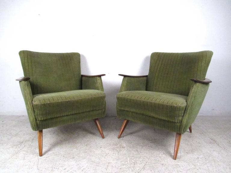 This stunning pair of vintage Danish armchairs features unique tapered legs, sculpted wooden arms, and wraparound wood trim. The vintage style and modern comfort of the pair make these a unique addition to any interior. Matching sofa available,