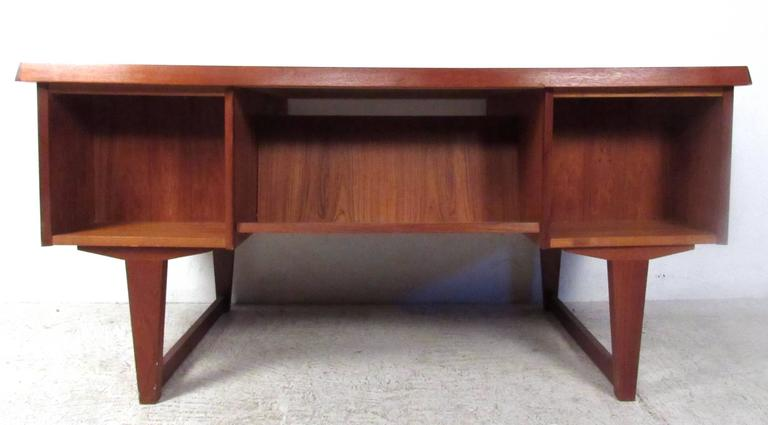 This stunning mid-century desk offers a unique workspace for home or office. The stylish tapered sled leg design is highly sought after, while the added shelves on the rear of the desk offers storage or display space. Carved drawer pulls and vintage