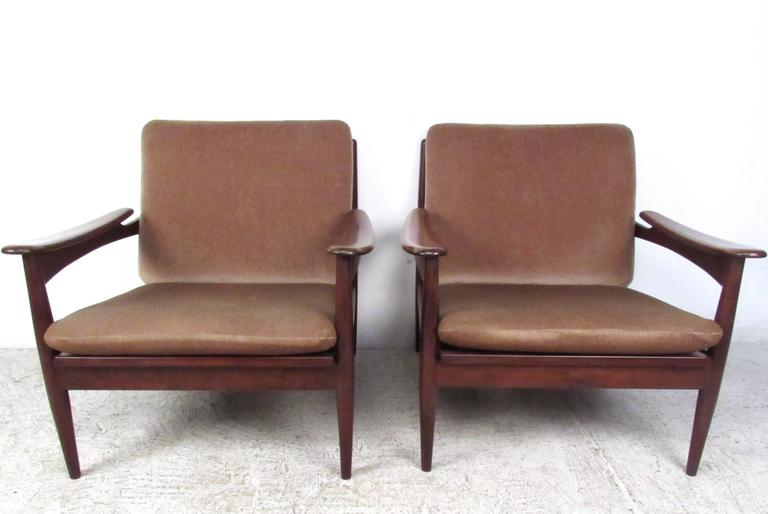 This stunning pair of vintage teak lounge chairs features sculpted/tapered frames, comfortable strap seats, and unique Mid-Century lines. The vintage fabric wonderfully compliments the unique shape and armrests. Please confirm item location (NY or