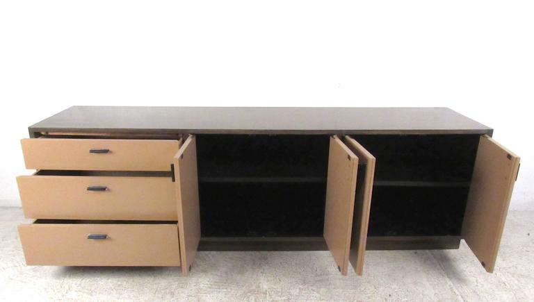 This uniquely sized vintage credenza offers a stylish combination of cabinet and drawer storage. Low profile height makes this perfect for use in an office or business environment, while it's hardwood finish contrasts wonderfully with it's lacquered