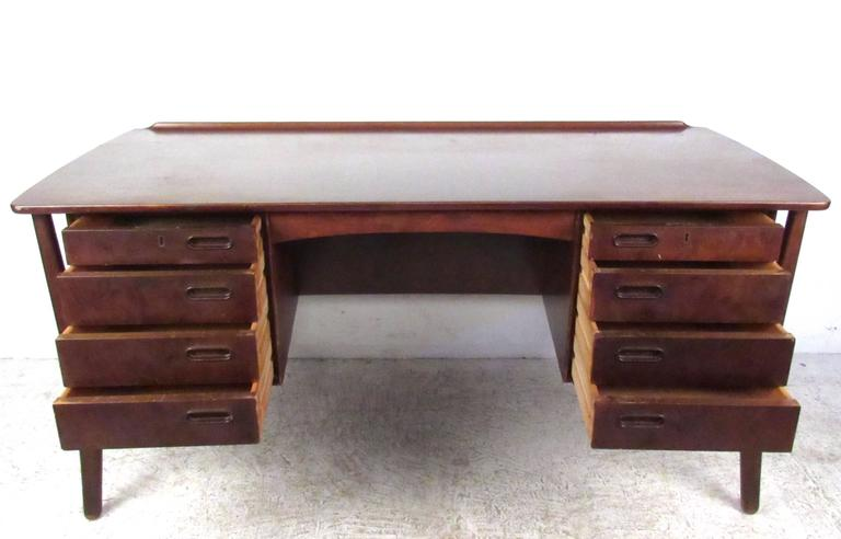 This stylish vintage desk by Svend Aage Madsen features a unique floating frame design with wonderful sculpted legs. Eight drawers and an addition cabinet/shelf space on the back side of the piece compliment the spacious desktop work area with