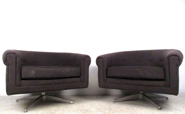This comfortable pair of swivel style lounge chairs by Selig make a stylish addition to any setting. Rounded back seats with sturdy metal bases, this unique matching pair is perfect for home or office. Please confirm item location (NY or NJ).