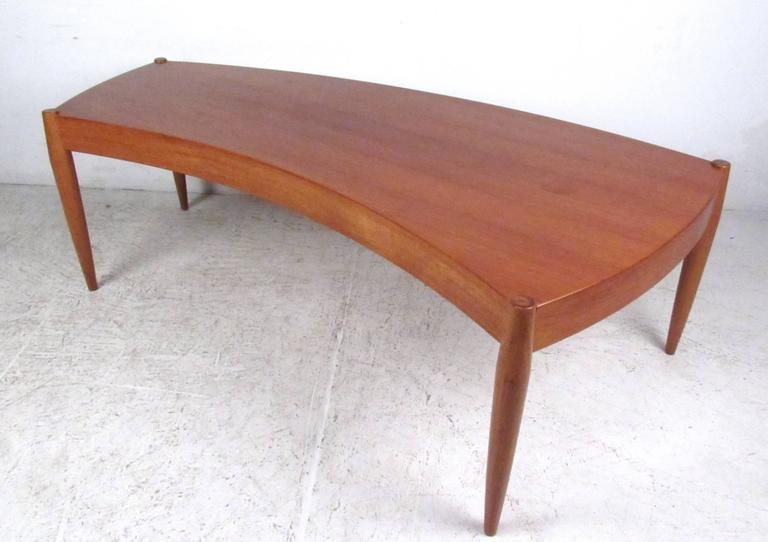 This beautiful vintage coffee table features a wonderful sculpted edge construction paired with tall tapered legs. Beautiful wood tone and unique shape makes this the perfect partner to the matching sofa and lounge chairs we also have available.