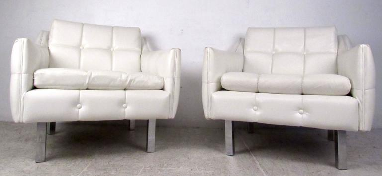 Two vintage-modern lounge chairs featuring chrome legs and tufted white vinyl upholstery with removable cushions make a stylish seating addition to home or office. Comfortable club chairs, matching sofa also available, contact dealer for details.