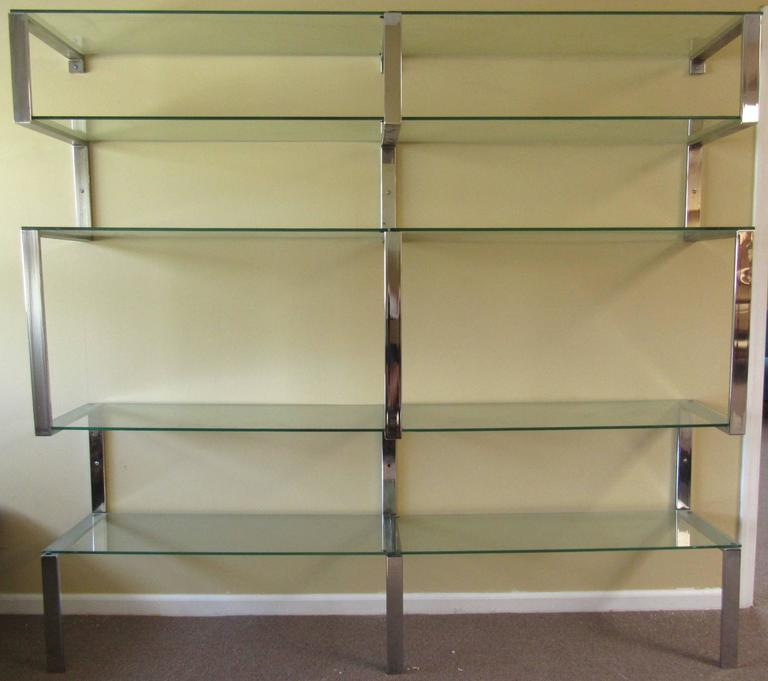 This stylish three-piece chrome finish shelving unit makes a clean modern addition in the style of mid-century designer Milo Baughman. Bent chrome wall shelf secures to support glass shelves, perfect for home or shop display. Please confirm item