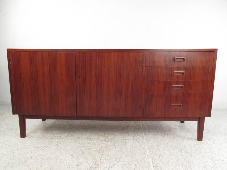 This vintage credenza features a unique reddish teak finish, with dual door cabinet storage, four carved pull drawers, and a miniature foot print perfect for tight spacing. Excellent Mid-Century piece for use as a television stand, service cabinet,
