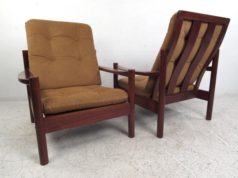 This tufted pair of vintage teak armchairs feature unique Danish modern design, with tufted upholstery and sculpted armrests. The removable cushions are covered in plush light brown fabric. Stylish bentwood vertical backs perfectly compliment the