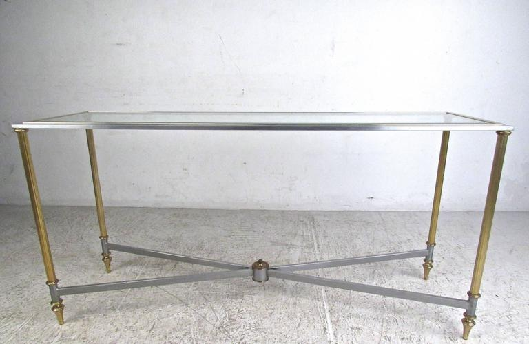 This unique vintage console table features a stunning slim design with unique brass legs and trim. Ornate tapered feet, grooved frame, and beveled glass top add to the beauty of this Mid-Century hall table in the style of Maison Jansen. Perfect
