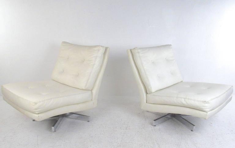 This beautiful pair of vintage vinyl swivel chairs for Thayer Coggin feature the stylish Mid-Century design of Milo Baughman. Tufted seats, slipper style design, and chrome swivel base add to the charm of the pair. Original tags still intact,