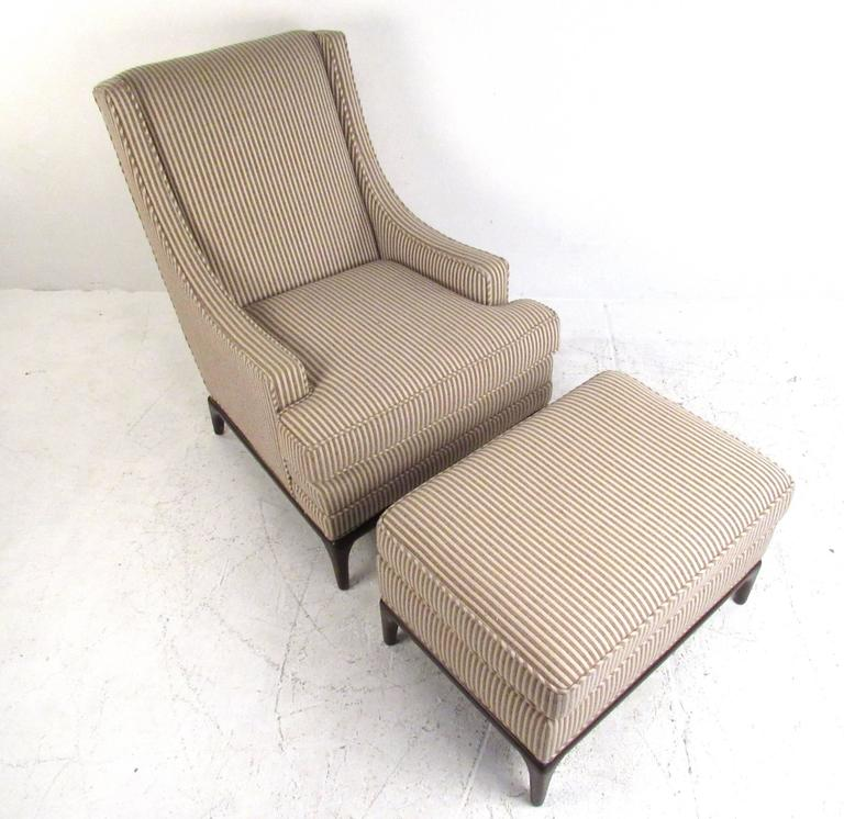 This vintage lounge chair features a unique sculpted design with high seat back and low-profile armrests. Tapered hardwood bases and vintage fabric add to the Mid-Century appeal of this Robsjohn-Gibbings style chair with matching ottoman. Please
