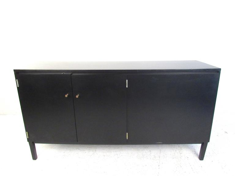 This vintage Paul McCobb Perimeter Group credenza features double-sided cabinets, drawers for storage, and unique ebonized finish. Classic McCobb drawer pulls add to it's unique Mid-Century appeal. Perfect piece as an office room divider with