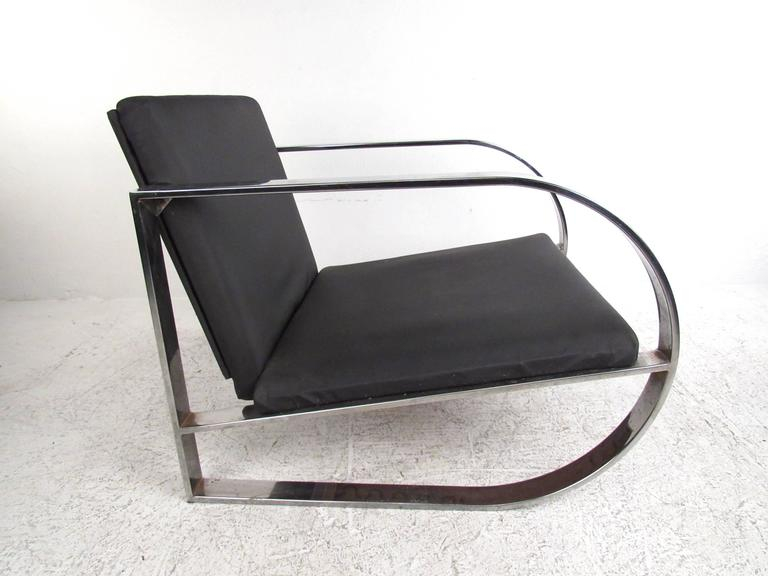 This sleek and stylish modern lounge chair features a unique chrome frame with an extra wide seat. Mid-Century Modern design with comfortable upholstery makes this a wonderful addition to any setting. Please confirm item location (NY or NJ).
