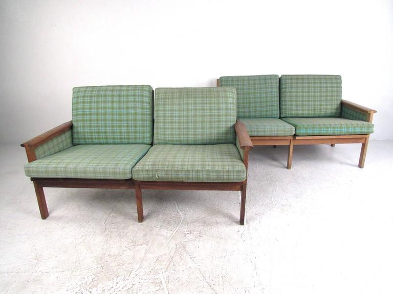 This stunning pair of vintage Danish teak settees make a beautiful Mid-Century addition to seating at home, office, or business. Unique upholstered frames, sculpted armrests, and versatile size make this matching pair the perfect set for rounding