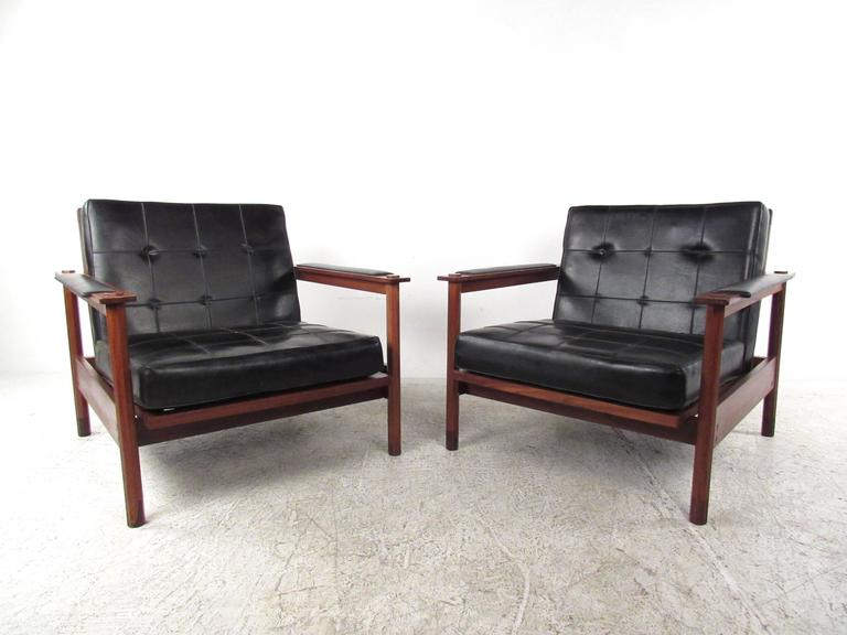This beautiful pair of walnut and vinyl lounge chairs make a stunning vintage addition to any seating arrangement. Tufted fabric seats also feature multiple seat back angles, vinyl armrests, and octagonal post construction. Comfortable Mid-Century