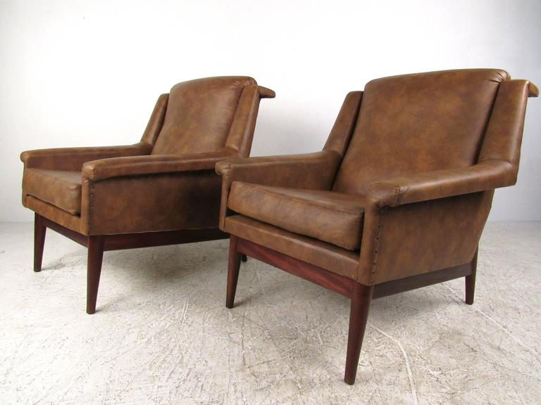 This unique pair of vintage vinyl lounge chairs feature wide upholstered seats with unique sculpted armrests. Vintage vinyl with brass studs adds to the classic appeal of the pair, while tapered hardwood legs showcase the Mid-Century influence on