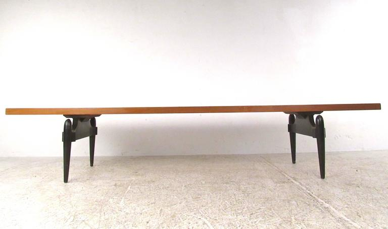 This beautiful vintage coffee table features a unique sculpted black lacquered base. Simple yet stylish design makes this long coffee table the perfect addition to any sofa seating area. Please confirm item location (NY or NJ).