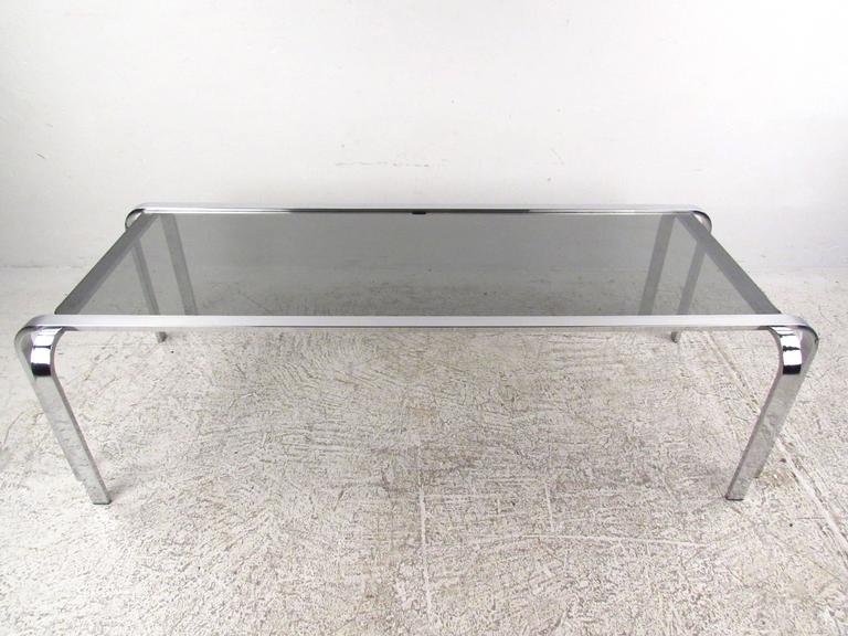 This stunning vintage chrome coffee table features uniquely designed metal frame with rounded corners and stylish double leg design. Glass top compliments the simplistic modern design of the piece and makes it a great addition to any interior.