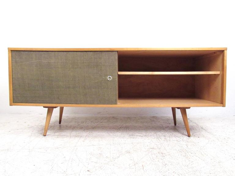 This vintage maple wood Paul McCobb cabinet features stylish grass cloth sliding doors with plenty of shelf storage for any setting. Tapered and angled legs add to the stylish simplicity of the piece, original Paul McCobb stamp on back. Please